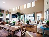 Esstisch und Stühle aus Holz neben gemütlicher Loungeecke in offenem Wohnhaus und nach oben offen