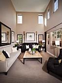 Elegantes Wohnzimmer in Hellgrau - graues und schwarzes Sofa um Couchtisch, an Wand Spiegel und gerahmte Bilder zwischen Wandbeleuchtung in mehrstöckigem Wohnraum