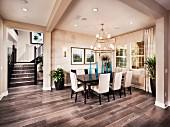 Essbereich mit weissbezogenen Polsterstühlen und Tisch mit gedrechselten Beinen auf grauem Holzboden im Vorraum mit Fenstern, im Hintergrund Blick durch breiten Durchgang auf Treppe