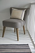 Striped linen cushion on retro easy chair with taupe upholstery; striped, woven rug in foreground