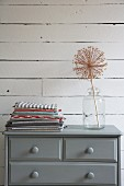Dried allium seed head in glass vessel and stacked folded tea towels on grey-painted chest of drawers