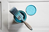 Flat paintbrush with pastel blue paint residue on open pot of paint