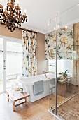 Floral gemusterte Vorhänge und ein Kronleuchter als Kontrast zu Designerbadewanne und moderner Duschabtrennung aus Glas