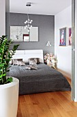 A double bed with a grey quilt and shimmering silver, decorative cushions in an elegant bedroom with pictures and a mirror on the wall