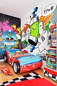 A children's room with a bright graffiti mural on the wall and a racing car bed