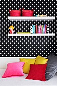 Decorative wall shelves on a wall hung with black and white spotted wallpaper above a sofa-bed with coloured cushions