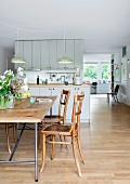 Egon Eiermann table frame with wooden top and old wooden chairs in front of open-plan kitchen in spacious interior