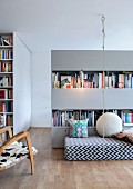Open-plan interior with climbing rope suspended from ceiling, patterned futon and partition shelving