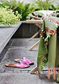 Colourful fabric slippers next to lounger with blanket on stone-flagged terrace