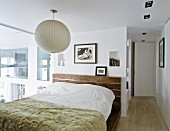 Bedspread on double bed below white spherical lamp in bedroom