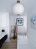 Modern bathtub below white, spherical lamps, washstand to one side and unfinished branch used as clothes rack in background