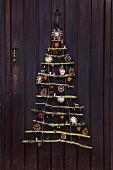 Stilisierter Weihnachtsbaum aus vermoosten Ästen mit Naturdeko und Strohsternen an einer Haustür
