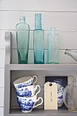 Collection of glass bottles and blue and white cups on wall-mounted shelves on wooden wall