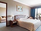 Bett mit gesteppter Tagesdecke in Hotelzimmer mit Balkon & Durchgang zum Wohnbereich