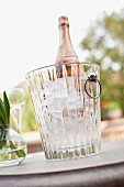 Vase and wine bottle in ice bucket on outdoor table