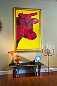 Vases on console table by candlestick holder below painting on wall; West Palm Beach; USA