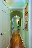 Wooden floor with paintings on green wall in narrow hallway; West Palm Beach; USA