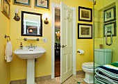 Washbasin, toilet and paintings mounted on yellow wall in bathroom; West Palm Beach; USA