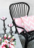 Black wicker chair with pink cushions and grey candlesticks