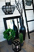 Black lantern, mirror with black-painted frame and black vase in front of white wooden wall