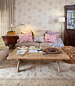 Comfortable, beige living room with modern standard lamp, patterned wallpaper and scatter cushions providing accents of colour