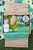 Wrapped drinks & food in wooden crate used as picnic hamper