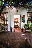 Sommerlicher Terrassenplatz mit verwittertem Natursteinbelag, aufgehängten Stiefeln und Einblick in beleuchtete Diele