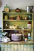 Vintage kitchen cupboard with open shelving on top, crockery and old kitchen scales