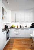 Spacious, white modern kitchen with corner counter, wall units and parquet flooring