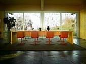 Dining room in wooden house with orange shell chairs at long dining table in front of glass wall with view of garden