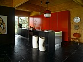 Cylindrical bar stools with footrests on slate floor at black, free-standing kitchen island in front of red fitted cupboards on wooden wall in open-plan interior