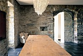 Chandelier above long table top and Baroque armchair against rustic stone walls in Ligurian farmhouse