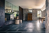 Sparsely furnished interior with charcoal stone floor in converted Italian farmhouse; stone walls contrasting with mirrored cupboards