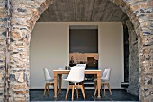 View through frameless glazing in stone arch of dining table with modern shell chairs; view into kitchen beyond