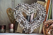Heart-shaped wreath of silver-painted larch cones in front of books on shelf
