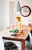 Autumnal arrangement and tealights on untreated wooden table