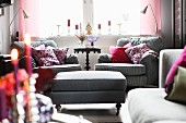 Country-house-style room with comfortable, grey striped armchairs, ottoman and reading lamps