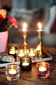 Romantic candlelight atmosphere with candlesticks and several tealight holders on rustic wooden table