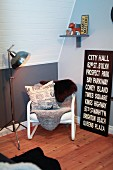 Teenager's bedroom in grey and white with wooden floor, comfortable reading chair with sheepskins and black and white picture with lettering leaning on wall