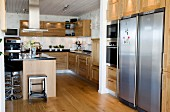 Geräumige offene Küche mit Holzfronten und Parkettboden, an der Küchentheke moderne schwarze Barhocker mit Edelstahlfuß