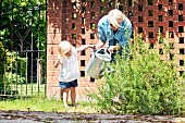 Little girl helping mother with watering can in garden