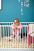 Kleines Mädchen klettert an den Gitterstäben vom Kinderbett hoch