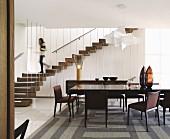 Esstafel mit gepolsterten Stühlen auf gemustertem Teppich, im Hintergrund Frau auf gewendelte Treppe mit vertikalen Metallstäben als Abtrennung