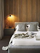 Classic table lamp on bedside cabinet next to bed with upholstered headboard against wood-clad wall