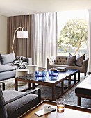 Coffee table with stone top and wooden frame, sofa set and glass wall with a view