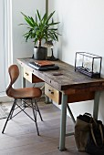 Vintage chair with wooden shell seat at desk with potted house plant in corner