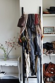 Numerous scarves hung on wooden ladder flanked by vintage table and bags on shelving