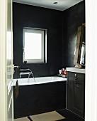Black-painted bathroom with washstand and bathtub below window