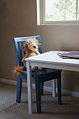 Soft toy sitting on kid's chair at table by window