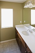 Mirror with wall lamps over washbasin in the bathroom